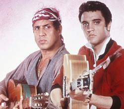 Adriano Celentano, lângă un poster al idolului său, Elvis Presley (1984)